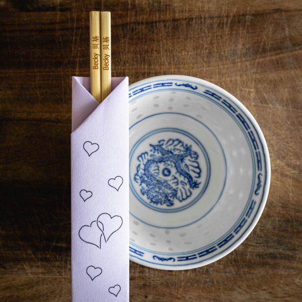 A pair of wooden chopsticks inside a lilac paper chopstick sleeve with a heart pattern