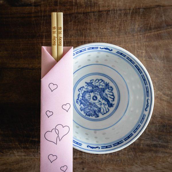 A pair of wooden chopsticks inside a pink paper chopstick sleeve with a heart pattern