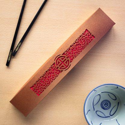 A bronze laser cut intricate chopstick presentation box
