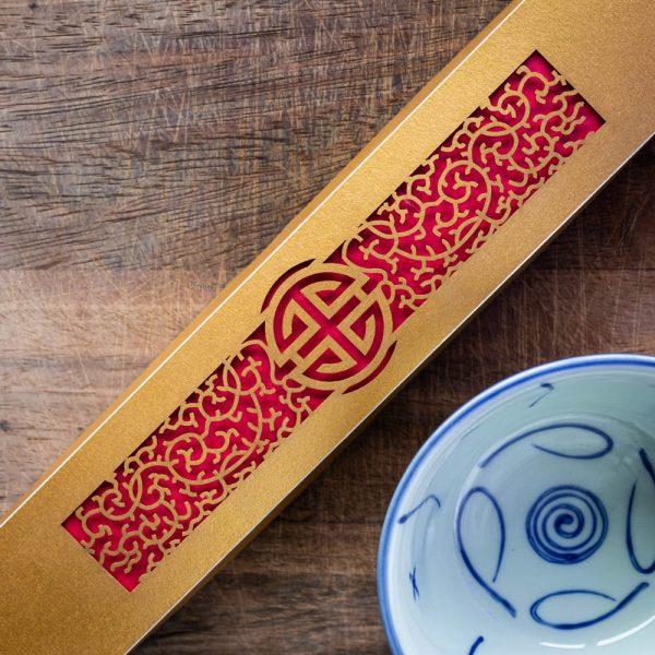 A gold laser cut intricate chopstick presentation box