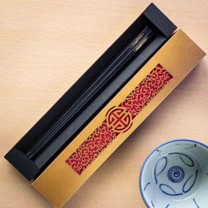 A gold laser cut intricate chopstick presentation box with chopsticks inside