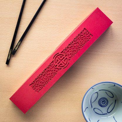 A red laser cut intricate chopstick presentation box