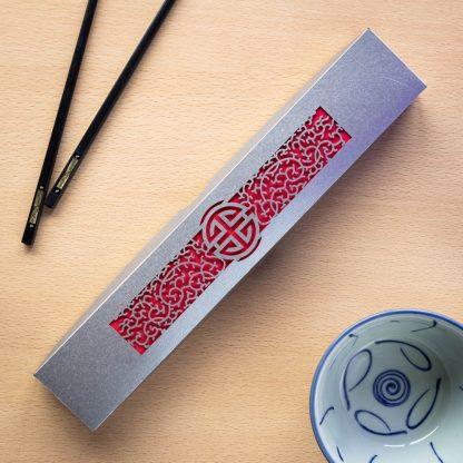 A silver laser cut intricate chopstick presentation box